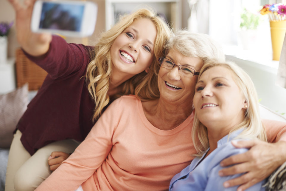 Blonde girl taking selfie with mom and grandma